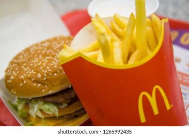 Russia, Saint-Petersburg, December 24, 2018: Hamburger menu in McDonald's restaurant Fries, coffee capuccino, Big Mac. Fastfood and junk food concept