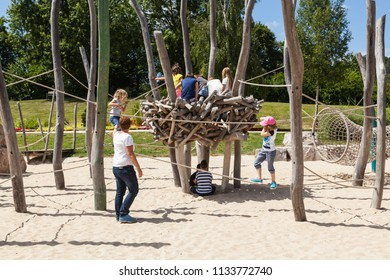 Russia, Samara, April 2017: children and their parents play in the playground in the city park on a spring sunny day.