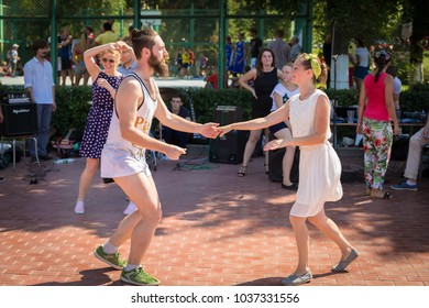 Russia, Samara, August 2016: a group of young people dancing on the embankment of the Volga River. Summer sunny day.