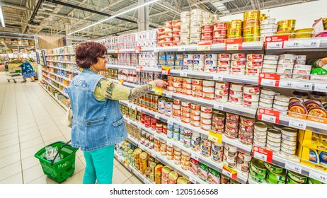 Russia, Samara, August, 2018: beautiful mature woman chooses canned meat in a large supermarket