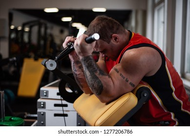 RUSSIA, SAMARA - DECEMBER 18, 2018: athletic man trains in the gym. Training of biceps on the bench