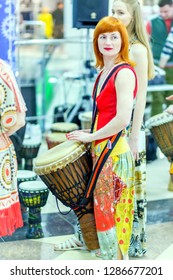 Russia, Samara, February 2018: A girl in ethnic clothes beats the tomtom drum.