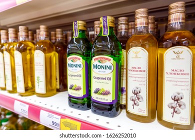 Russia Samara January 2020. Bottles of imported olive and cottonseed oil on a shelf in a store. Text in Russian: cottonseed oil, refined, price of goods, on a pallet