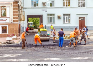 Russia, Samara, July 2017: A team of workers with the help of special equipment is laying asphalt at the entrance to the yard. on a summer day. Text in Russian: Chapaevskaya Street.