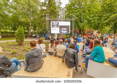 "Russia, Samara, July 2017: young people listen to a lecture on the embankment at the festival ""Volgafest"" on a summer day. Text in Russian: today the factories are turning into lofts."
