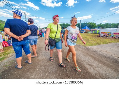 Russia, Samara, July 2019: Grushinsky festival. Festival guests stroll through the festival clearing. Text in Russian: sport