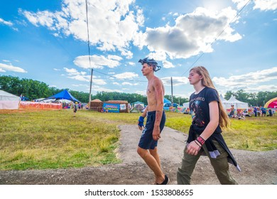 Russia, Samara, July 2019: Grushinsky festival. Festival guests stroll through the festival clearing. Text in Russian: playground