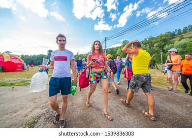 Russia, Samara, July 2019: Grushinsky festival. Guests of the festival, young people go through the festival meadow.
