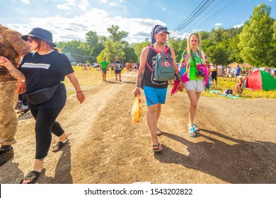 Russia, Samara, July 2019: Grushinsky festival. Festival guests - a young couple with backpacks go through the campground.