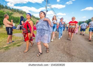 Russia, Samara, July 2019: Grushinsky festival. Festival guests stroll through the festival clearing.