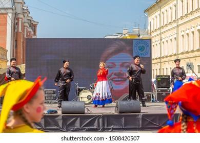 "Russia, Samara, July 2019: Samara Song and Dance Ensemble ""Volga Cossacks"" at the gastronomic festival ""Fair of Tastes"". Text in Russian: Samara product"