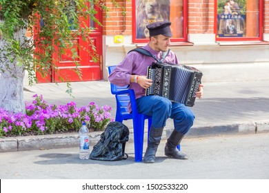 Russia, Samara, July 2019: A young man in a Russian national costume plays the harmonica on a city street.