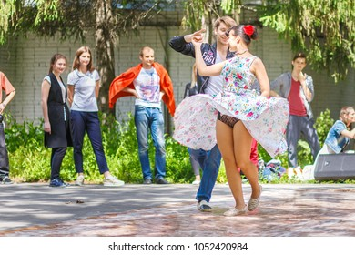 Russia, Samara, June 2017: a young beautiful couple dancing an American slow dance in Gagarin's Park on a sunny summer day.