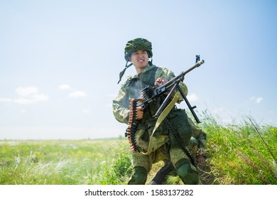 Russia, Samara, June 2019: a young Russian soldier fires a burst from a machine gun. Text in Russian: start, race of heroes, throw