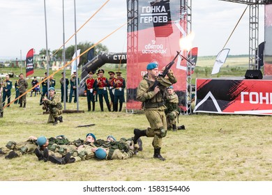Russia, Samara, June 2019: a young, strong, Russian soldier shoots a burst of machine gun. Text in Russian: start, race of heroes, throw