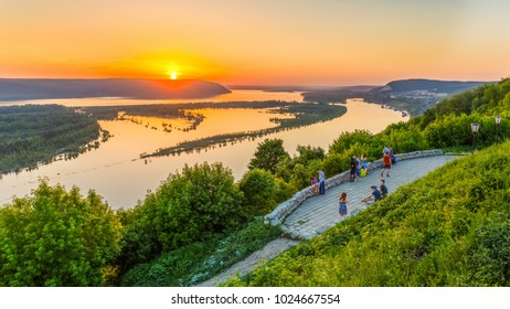 Russia, Samara, May 26, 2016: View of the Volga River from an observation platform near Samara, sunset over the Zhigulev mountains, spring flood of the river. The townspeople rest and admire the Volga