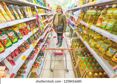 Russia, Samara, November 2018: a beautiful mature woman chooses products in a large supermarket. Text in Russian: pate, rice, stew
