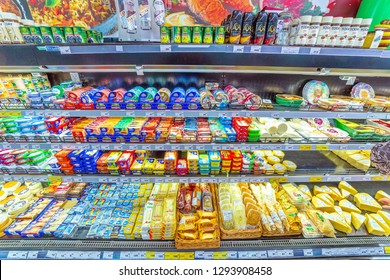 Russia, Samara, November 2018: a variety of cheeses in the refrigerated display case In a large supermarket. Text in Russian: Chechil cheese, Friendship, Lambert, syrobatov, with ham, olives,  Adygei,