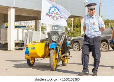 "Russia, Samara, September 2017: Soviet policeman in uniform on a Soviet police motorcycle ""Ural"" on a sunny day. The text in Russian: samara militia."