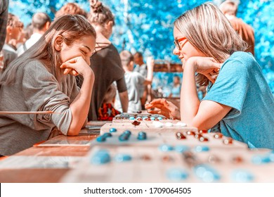 """Russia, Samara, September 2018: A group of children playing the board logic game """"The Mill"""" in the park."""