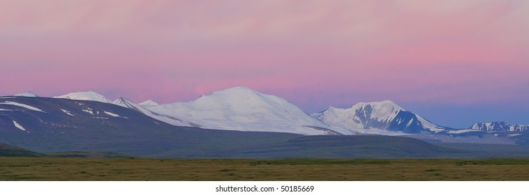 Russia. Siberia. Altai. View on white snow summits of Tavan-Bogdo-Ula mountain ridge (five holy summits, in mongolian)  at a sunrise in rose tint
