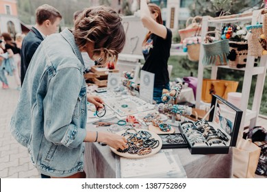 Russia, Sochi - 2 may 2019 Girl looking at the colourful handmade jewelry on the local fair outside. Horizontal orientation.