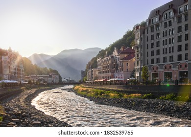 RUSSIA, SOCHI - JULY 16, 2020: view of hotels, cafes, shops, river in the resort of Rosa Khutor. The rays of the evening sun