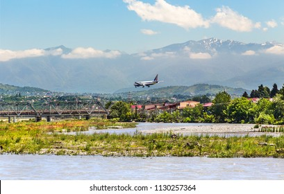 Russia, Sochi - June 08, 2015: Airplane comes to land above the homes and river in the resort of Adler.