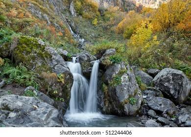 "Russia, Sochi, resort ""Krasnaya Polyana"". In the mountains of the Caucasus come autumn. Waterfall ""Polikarya"", the background  blurred."