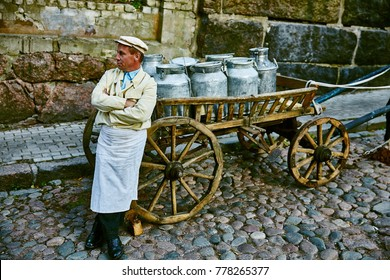 RUSSIA SOMETHING. JULY 10, 2014. A male milkman is standing next to a cart with milk cans