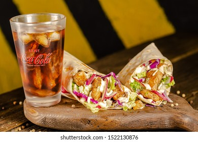 Russia St. Petersburg 011019 Coca Cola bottle, a glass on a vintage wooden table, on a cutting board, juicy kebab shawarma, with pieces of meat, dark light close-up, fully, cut, whole, cherry tomatoes