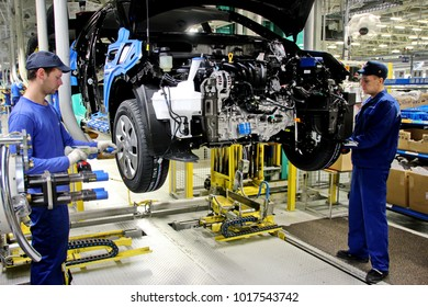 "Russia, St. Petersburg - April 02, 2015. Automobile plant ""Hyundai Motor Manufacturing Rus"" . Cars Production. Assembly of cars on the conveyor.  Installation of wheels."