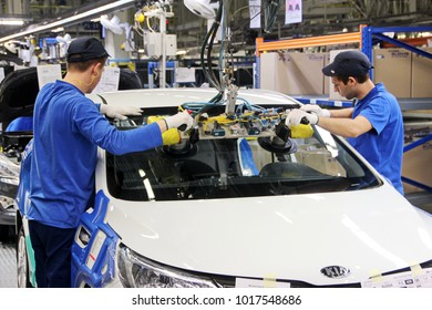 """Russia, St Petersburg - April 02, 2015. Automobile plant """"Hyundai Motor Manufacturing Rus"""" . Cars Production. Assembly of cars on the conveyor. Workers install the KIA Rio wind and rear windows"""