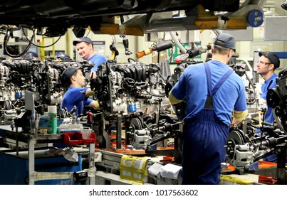 "Russia, St Petersburg - April 02, 2015. Automobile plant ""Hyundai Motor Manufacturing Rus"" . Cars Production. Assembly of cars on the conveyor. Worker assembly engines."