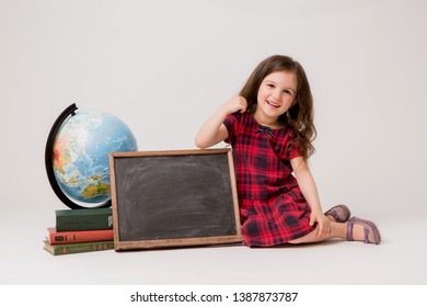 Russia, stavropol, home studio. 24\04\2019. baby girl brunette with globe books and blank chalk drawing Board in school uniform, preschool education concept,space for text