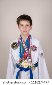 Russia, Stavropol - May 20, 2018:boy in a kimono with medals in a photo studio. An athlete achieving success in taekwondo.