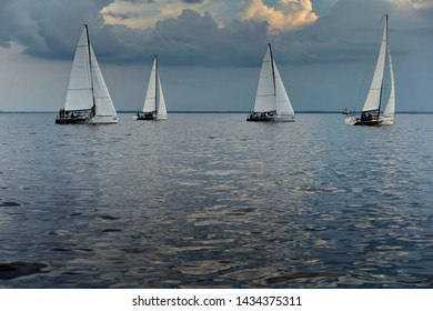 Russia, St.Petersburg, 21 June 2019: Four sailing sports boats in the sea against the beautiful sky with clouds