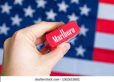 RUSSIA, ST.PETERSBURG -  31, January 2019: A hand is holding a red pack of Marlboro cigarettes against the background of the USA flag.