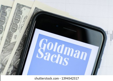 RUSSIA, ST.PETERSBURG, April 4, 2019: site with Logo of the Goldman Sachs Group in the smartphone lying on paper with charts and one hundred dollar bills.