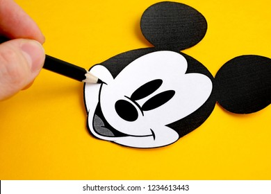 RUSSIA, ST.PETERSBURG - NOVEMBER 19, 2018: Black and white face of Mickey Mouse out of paper near finger hold pencil on a yellow background