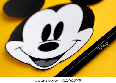 RUSSIA, ST.PETERSBURG - NOVEMBER 19, 2018: Black and white face of Mickey Mouse out of paper near pencil on a yellow background