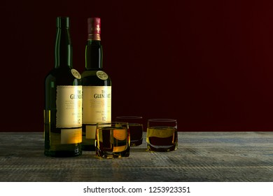 Russia, Surgut, December 10, 2018: A bottles of Glenlivet whiskey 12-year-old with glasses filled with this drink, on a dark red background with copy space. 3D-visualization.