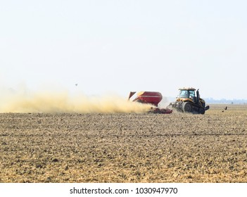 Russia, Temryuk - 19 July 2015: Tractor rides on the field and makes the fertilizer into the soil. Clouds of dust from the dry soil tractor trailer. Fertilizers after plowing the field.