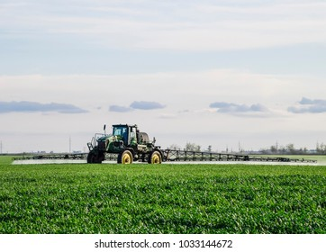 Russia, Temryuk - May 10, 2017: Tractor with high wheels is making fertilizer on young wheat. The use of finely dispersed spray chemicals. Tractor with a spray device for finely dispersed fertilizer