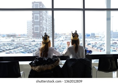 Russia, Tyumen, 30.03.2019. Teenage girls in crowns from Burger king for lunch at the Mall. Girls eat in the shopping center. Rear view. Fast food.