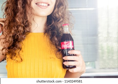 Russia, Tyumen - July 25, 2018: Beautiful woman drinking coca cola bottle