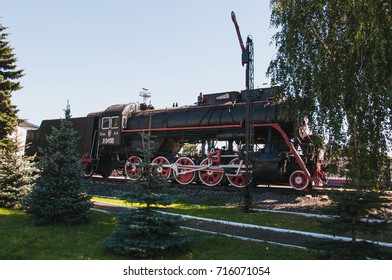 RUSSIA, VLADIMIR, - August 12, 2017: old Soviet steam locomotive with a trailer for coal is on the tracks among the trees.