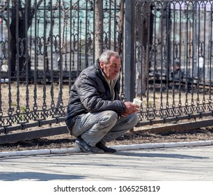 Russia, Vladivostok, 04/08/2018. Dirty poor man begging alms in the street. Poverty and poor people. Beggars on the streets of the city. Social problems concept.