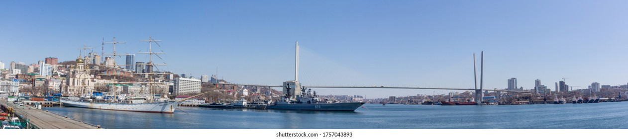 """Russia, Vladivostok, 04/08/2020. Panoramic view on downtown of Vladivostok. Sailing ship """"Nadezda"""", modern battle ships of Russian Navy in the port and famous Golden Bridge accross Golden Horn bay."""