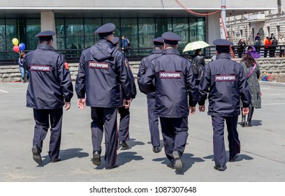 "Russia, Vladivostok, 05/09/2018. Policemen on service in city downtown. Inscription ""National Guard"" on uniform jacket."